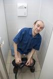 Erschrockener Mann in der Toilette Stockfotos