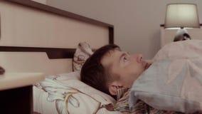 Erschrockener Mann hört merkwürdiges etwas und versteckt sich unter der Decke stock footage