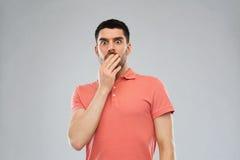 Erschrockener Mann im Polot-shirt über grauem Hintergrund lizenzfreies stockfoto
