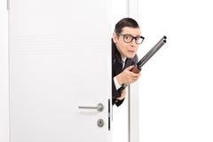 Erschrockener Mann mit dem Gewehr, das einen Raum betritt Stockfotografie