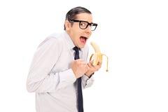 Erschrockener Mann mit Gläsern eine Banane essend Stockbild