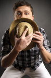 Erschrockener Mann versteckt hinter seinem Strohhut Stockbild