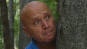 Erschrockener Mann versteckt sich nach einem Baum im Wald lizenzfreie stockfotos