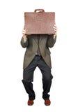 Erschrockener Mann versteckte sich hinter einem Koffer Stockbilder