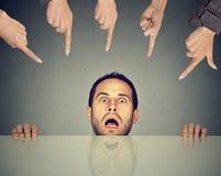 Erschrockener Mannangestellter, der unter der Tabelle beschuldigt wird von den Leuten sich versteckt, die Finger auf ihn zeigen Stockfoto