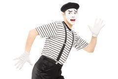 Erschrockener männlicher Pantomimekünstler, der weg läuft Stockfoto