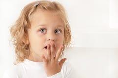 Erschrockenes überraschtes kleines Mädchen auf weißem Hintergrund Stockbild