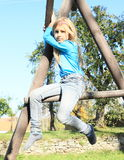 Erschrockenes Mädchen, das auf kletterndem Rahmen sitzt Stockfotos