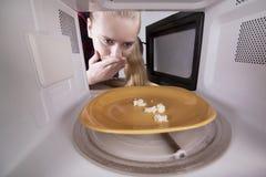 Erschrockenes Mädchen, das in der Mikrowelle schaut Zerkrümelt Weißbrot auf Platte im Ofen stockfoto