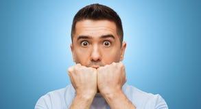 Erschrockenes Manngesicht über blauem Hintergrund lizenzfreie stockfotos