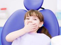 Erschrockenes Mädchen im Büro des Zahnarztes Stockfoto