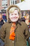 Erson нося голландский лицевой щиток гермошлема короля Willem-Александра на Kingsday на блошинном улицы Стоковые Изображения RF