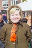 Erson som bär en holländsk konung Willem-Alexander, vänder mot maskeringen på Kingsday på en gataloppmarknad royaltyfria bilder