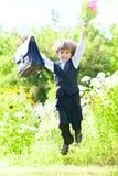 Erst-Formschüler mit Blumen und Schultasche Lizenzfreie Stockfotos
