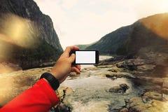 Erst-Personenansicht, der Mann macht ein Foto von einem Gebirgsfluss auf smartfon Konzept, weißer Schirm Smartphone Stockfoto