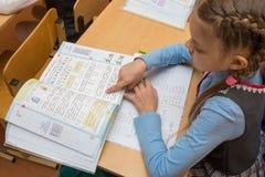 Erst-Sortierer an einer Lektion des Mathematiklesejobs, der seinen Finger unter den Text laufen lässt Stockfotografie