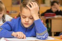 Erst-Sortierer an einer Lektion liest den Text und lässt seinen Finger nach den Grundsätzen laufen Lizenzfreies Stockbild