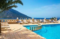 Erstaunliche Ansicht über schwimmenden Poolbereich und sunbeds unter Palme w Stockbild