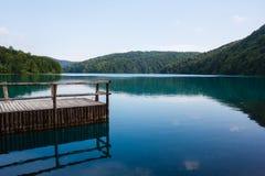 Erstaunliche Ansicht des kleinen alten hölzernen Piers und der Landschaft des Waldes und des Sees umgeben durch Berge in National Lizenzfreies Stockbild