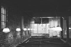 Erstaunliche Ansicht des Lagerdeckenraumes mit Ziegelstein, Stahlträgern und hängenden industriellen Lichtern in Schwarzweiss stockfoto