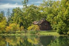 Erstaunliche Ansicht einer hölzernen verlassenen Kabine der alten Weinlese, stehend im Holz reflektiert im Seeruhewasser am sonni Lizenzfreies Stockbild