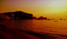 Erstaunliche Ansicht Vollkommene Landschaft Meer, Strand, Berge, Insel und orange Himmel mit Wolken Stockbilder