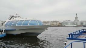 Erstaunliche Ansicht von das Fluss Neva-Kai in St Petersburg Ein Flussbus am Liegeplatz, wunderbare Architektur am Hintergrund stock footage