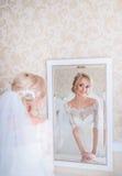 Erstaunliche blonde Braut schaut im weißen Spiegel Stockfotografie