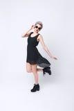 Erstaunliche blonde junge Frau, die schwarzes Kleid und Sonnenbrille trägt Stockfoto