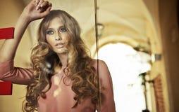 Erstaunliche blonde junge Frau hinter der Glaswand Lizenzfreies Stockbild
