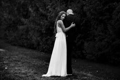 Erstaunliche Braut umarmt einen Bräutigam, der über seiner Schulter schaut Stockbild