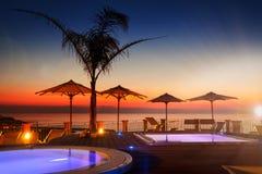 Erstaunliche Dämmerung mit Palme und Sonnenschirmen am Hintergrund mit Himmel Stockfotografie