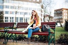 Erstaunliche Frau, die auf einer Bank außerhalb des Ablesens einer Zeitschrift, hörend Musik, trinkender köstlicher Kaffee sitzt  Lizenzfreie Stockbilder