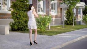 Erstaunliche Frau im schönen weißen Kleid geht kurz Weg, zwecks am Telefon mit ihrem Freund zu sprechen stock video