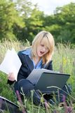 Erstaunliche Geschäftsfrau auf Gras mit Dokumenten lizenzfreies stockbild