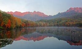 Erstaunliche Herbstseelandschaft von Kagami Ike Mirror Pond auf einem nebelhaften Morgen mit symmetrischen Reflexionen des bunten stockbilder