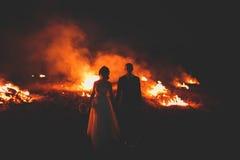 Erstaunliche Hochzeitspaare nahe dem Feuer nachts lizenzfreie stockbilder