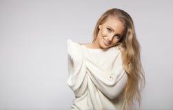 Erstaunliche junge blonde Aufstellung auf grauem Hintergrund Stockfotografie