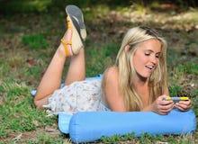 Erstaunliche junge blonde Frau in den sundress - texting Stockfotos