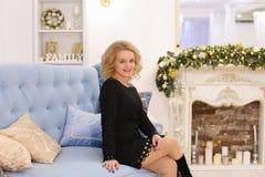Erstaunliche junge blonde Frau, die das Sitzen auf Couch lächelt und aufwirft Stockfotos
