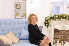 Erstaunliche junge blonde Frau, die das Sitzen auf Couch lächelt und aufwirft Lizenzfreie Stockbilder