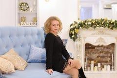 Erstaunliche junge blonde Frau, die das Sitzen auf Couch lächelt und aufwirft Stockbilder