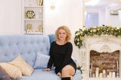Erstaunliche junge blonde Frau, die das Sitzen auf Couch lächelt und aufwirft Stockbild