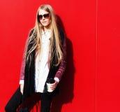 Erstaunliche junge blonde modische Ausstattung der Frauenabnutzung, moderne Gläser Auf dem roten Hintergrund im Freien Lizenzfreies Stockfoto