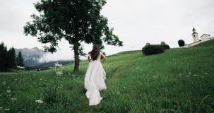 Erstaunliche junge Frau mit dem recht langen Kleid, das mitten in grünem Feld läuft stock footage