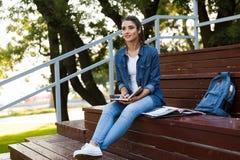Erstaunliche junge Schönheit, die Anmerkungen sitzt in Notizbuch draußen, schreibend stockfotografie