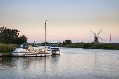 Erstaunliche Landschaft der Windmühle und des Flusses an der Dämmerung auf Sommer morni Lizenzfreies Stockbild