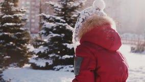 Erstaunliche Nahaufnahme schoss vom netten kleinen Mädchen, das im Schnee spielt und lief von der Kamera zur sonnigen Kiefernpark stock footage