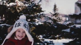 Erstaunliche Nahaufnahme schoss vom netten kleinen Mädchen in der Winterkleidung, die zur Kamera von hinten schneebedeckte Kiefer stock video footage