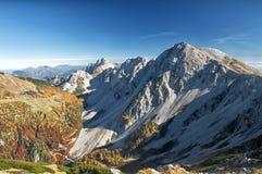 Erstaunliche Panoramaansicht eines herrlichen alpinen Gebirgszugs an einem sonnigen Herbsttag Stockfoto